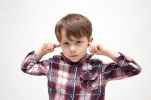 耳を塞ぐ少年