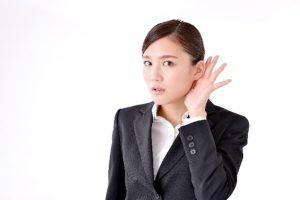耳に手をやる女性