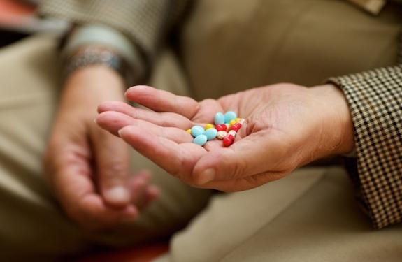 薬を手に持つ老人