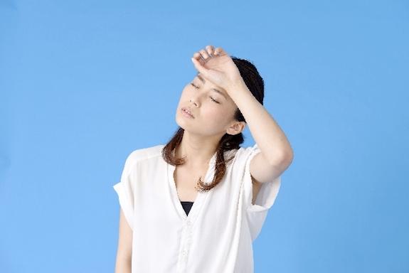 額を拭う女性