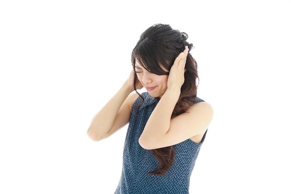 耳を防ぐ女性